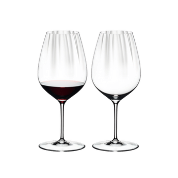 Two RIEDEL Performance Cabernet glasses side by side. The glass on the left side is filled with red wine, the other one is empty.