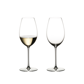 Two RIEDEL Veritas Sauvignon Blanc glasses stand side by side. The one on the left side is filled with white wine, the other one is unfilled.