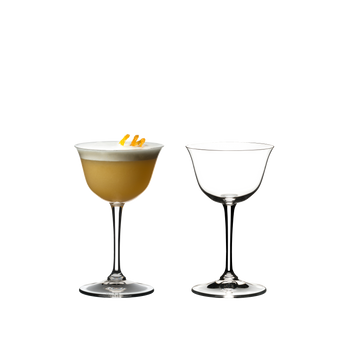 Two RIEDEL Drink Specific Glassware Sour glasses side by side on white background. The left one is filled with a Sour cocktail, the right glass is empty.