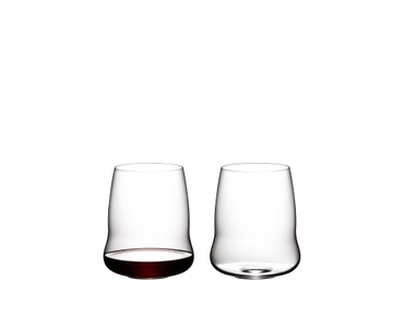 Two SL RIEDEL Stemless Wings Cabernet Sauvignon tumblers side by side on a white background. The glass on the right side is filled with red wine, the other one is empty.