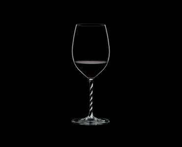 RIEDEL Fatto A Mano Cabernet/Merlot Black & White R.Q. filled with a drink on a black background