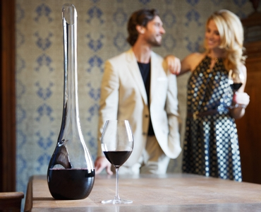 A wine filled RIEDEL Horse Decanter and a RIEDEL Veritas Old World Syrah glass stand on a table. A couple stands behind it.