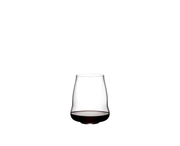 Blonde woman leans against a wall and smells a red wine from a SL RIEDEL Stemless Wings Pinot Noir /Nebbiolo tumbler.
