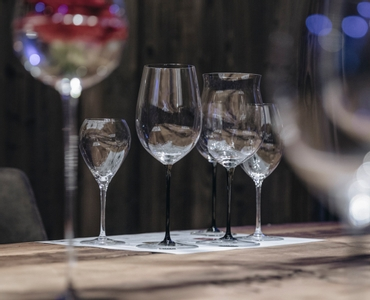 5 unfilled RIEDEL Sommeliers and Sommeliers Black Tie wine glasses on a sheet of paper atop of a wooden table.