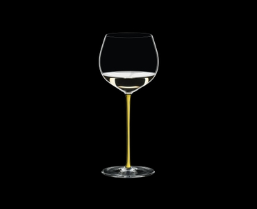 RIEDEL Fatto A Mano Chardonnay (im Fass gereift) Gelb R.Q. gefüllt mit einem Getränk auf schwarzem Hintergrund
