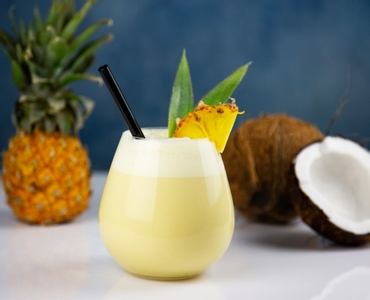 Decorated Pina Colada served in a RIEDEL O Wine Tumbler Pinot Noir glass. A pineapple and a coconut in the background.