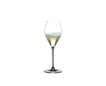 Two RIEDEL Heart to Heart Champagne Glasses. One is unfilled, the other one is filled with Champagne on white background.