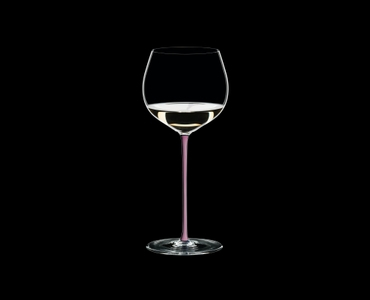 RIEDEL Fatto A Mano Oaked Chardonnay Pink R.Q. filled with a drink on a black background