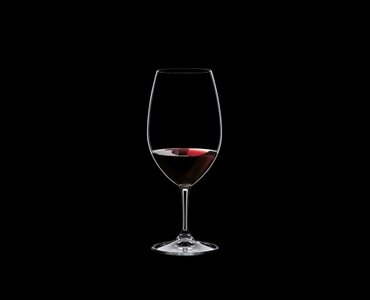 RIEDEL Restaurant Syrah filled with a drink on a black background