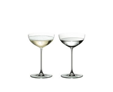 Two RIEDEL Veritas Coupe/Cocktail glasses side by side. The glass on the left side is filled with champagne, the other one is filled with a clear drink.