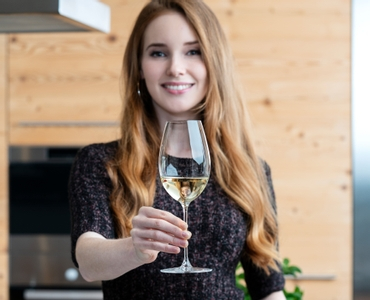 A young woman holds a white wine filled RIEDEL Veritas Sauvignon Blanc glass with an outstretched arm in front of her.