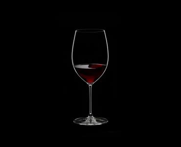 RIEDEL Veritas Restaurant Cabernet/Merlot filled with a drink on a black background