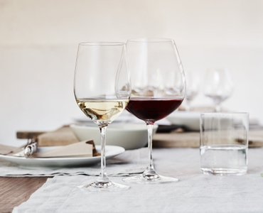 6 RIEDEL Vinum Viognier/Chardonnay glasses are slightly offset one behind the other on the right and two glasses on the left. A red plus sign is placed between the glasses. All 8 wine glasses are filled with white wine.