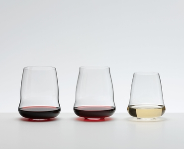 Wine filled SL RIEDEL Stemless Wings Cabernet Sauvignon glass, Pinot Noir / Nebbiolo and Riesling / Champagne Glass stand side by side on a grey surface.