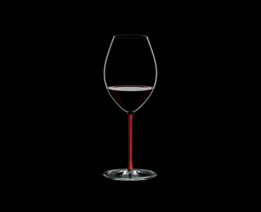 RIEDEL Fatto A Mano Old World Syrah Red R.Q. filled with a drink on a black background