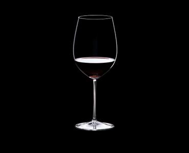 RIEDEL Sommeliers Bordeaux Grand Cru R.Q. 4er-Set gefüllt mit einem Getränk auf schwarzem Hintergrund