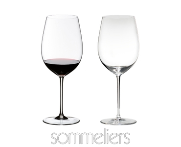 Two RIEDEL Sommeliers Bordeaux Grand Cru glasses on white background. The one on the left side is filled with red wine, the other one is empty. Below the glasses is the Sommeliers logo.