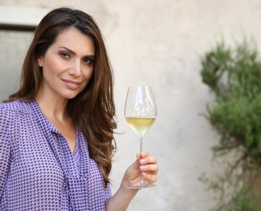 Woman outdoors in a violet summer blouse holds a filled RIEDEL Superleggero Champagne Wine Glass in her hand