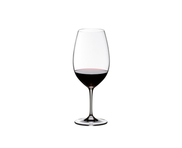 Man in a wine cellar leans against a hughe wine barrel and looks at the red wine in the RIEDEL Vinum Syrah glass he holds.