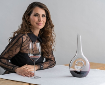 One red wine filled RIEDEL Sakura Decanter on white background