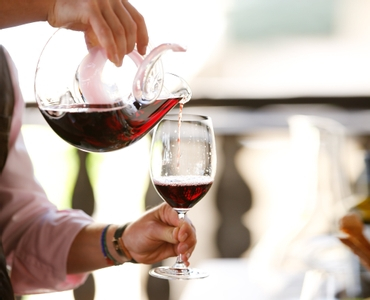 On a sunny day, a man pours red wine from a RIEDEL Curly Pink Decanter into a RIEDEL Vinum Cabernet Sauvignon/Merlot glass