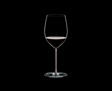 RIEDEL Fatto A Mano Cabernet Pink filled with a drink on a black background