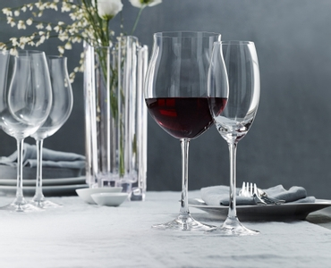 A red wine filled Nachtmann Vivendi Burgundy glass and an unfilled Vivendi Champagne Flute on a set dinner table