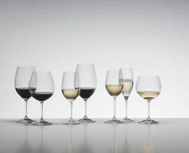 7 wine glasses of the RIEDEL Vinum range filled with red wine, white wine and sparkling wine stand on a grey ground