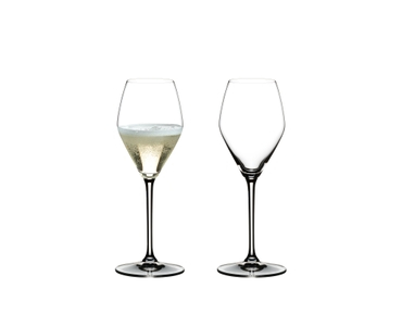Two RIEDEL Heart to Heart Champagne Glasses. One is unfilled, the other one is filled with Champagne.