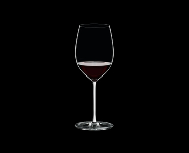 RIEDEL Fatto A Mano Cabernet/Merlot White filled with a drink on a black background