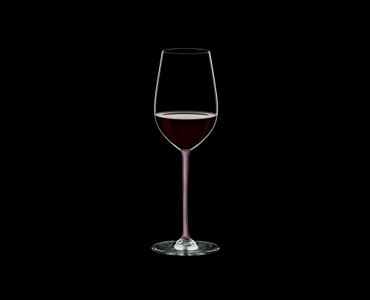 RIEDEL Fatto A Mano Riesling/Zinfandel Pink filled with a drink on a black background