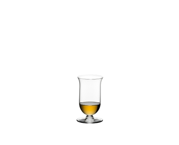 2 glasses of RIEDEL Vinum Single Malt Whisky and a carafe filled with whisky on a stone wall.