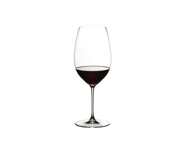 A red filled RIEDEL Veritas New World Shiraz Glass besides a red wine filled RIEDEL Ayam decanter on a wine barrel.