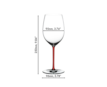 Six RIEDEL Fatto A Mano Cabernet/Merlot glasses with differently coloured stems (f.l.t.r.: red, yellow, black, green, white and dark blue) stand on a countertop in a modern, bright kitchen next to a red wine filled RIEDEL Decanter Amadeo Fatto A Mano.