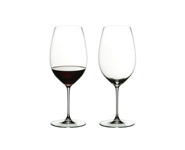 Two RIEDEL Veritas New World Shiraz glasses side by side. The glass standing on the left side is filled with red wine, the other one is empty.