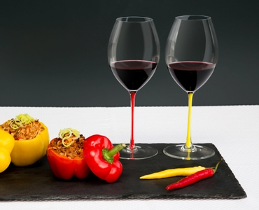 Two red wine filled RIEDEL Fatto A Mano Syrah glasses with a red and a yellow stem on a slate plate with stuffed peppers.