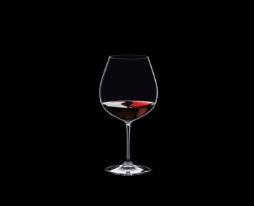 RIEDEL Vinum Restaurant Pinot Noir (Burgundy red) rempli avec une boisson sur fond noir