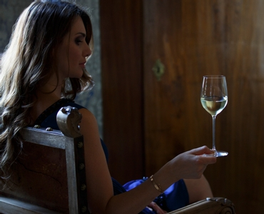 Lady in a summer dress sitting on an armchair and holding a white wine filled RIEDEL Veritas Viognier/Chardonnay glass