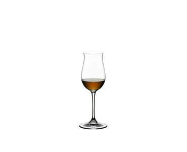 A RIEDEL Vinum Cognac Hennessy glass filled with cognac stands on a table between a typewriter and three open cognac bottles. The sun shines through the window into the room and makes the cognac in the glass shine.