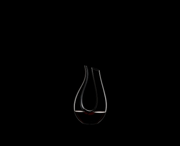 RIEDEL Decanter Black Tie Amadeo R.Q. filled with a drink on a black background