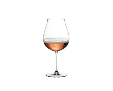 Woman sits on a table and looks at a red wine filled RIEDEL Veritas New World Pinot Noir glass, she grasps on the stem.