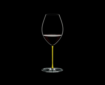 RIEDEL Fatto A Mano Syrah Yellow filled with a drink on a black background