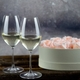 2 filled RIEDEL Vinum Champagne Wine Glasses stand on a wooden table next to a heart-shaped box filled with pink rose petals.