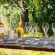 3 bottles of rosé wine and 4 filled RIEDEL Extreme Rosé Wine Glasses on a wooden bench in a summer garden.