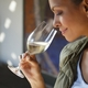 A woman holds a RIEDEL Vinum Riesling Grand Cru/Zinfandel glass under her nose to smell and look at the white wine.