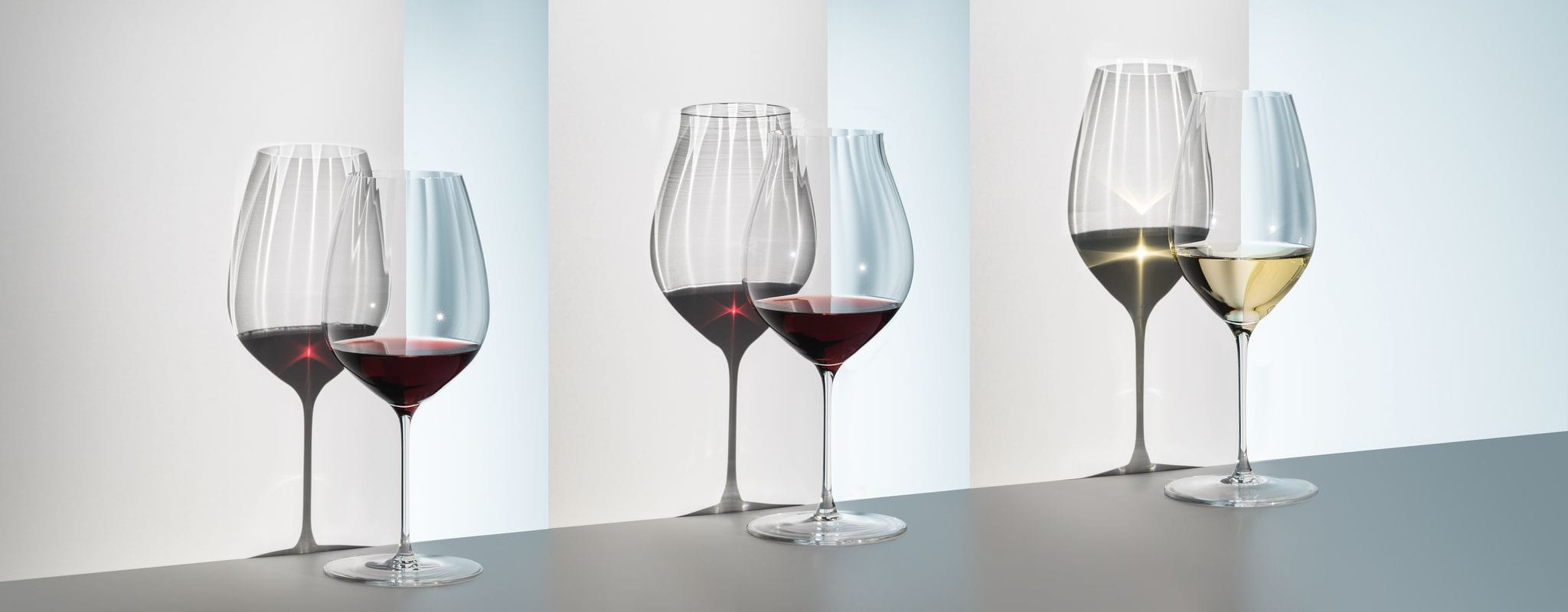 3 RIEDEL Performance Cabernet, Pinot Noir and Riesling glasses filled with wine cast shadows on a white wall, showing the structure of the bowl.