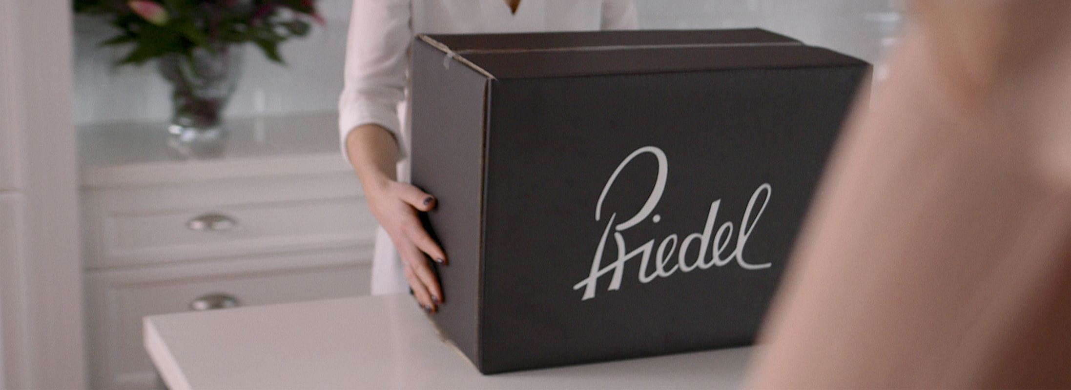 A woman holding a Riedel Premium Packaging box