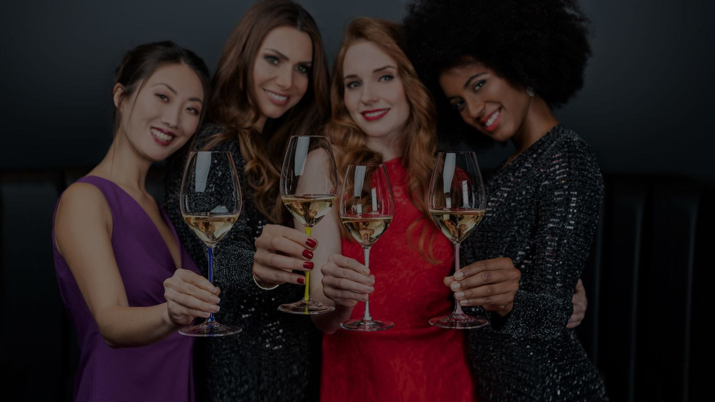 Women raising their filled RIEDEL Fatto A Mano Champagne glasses