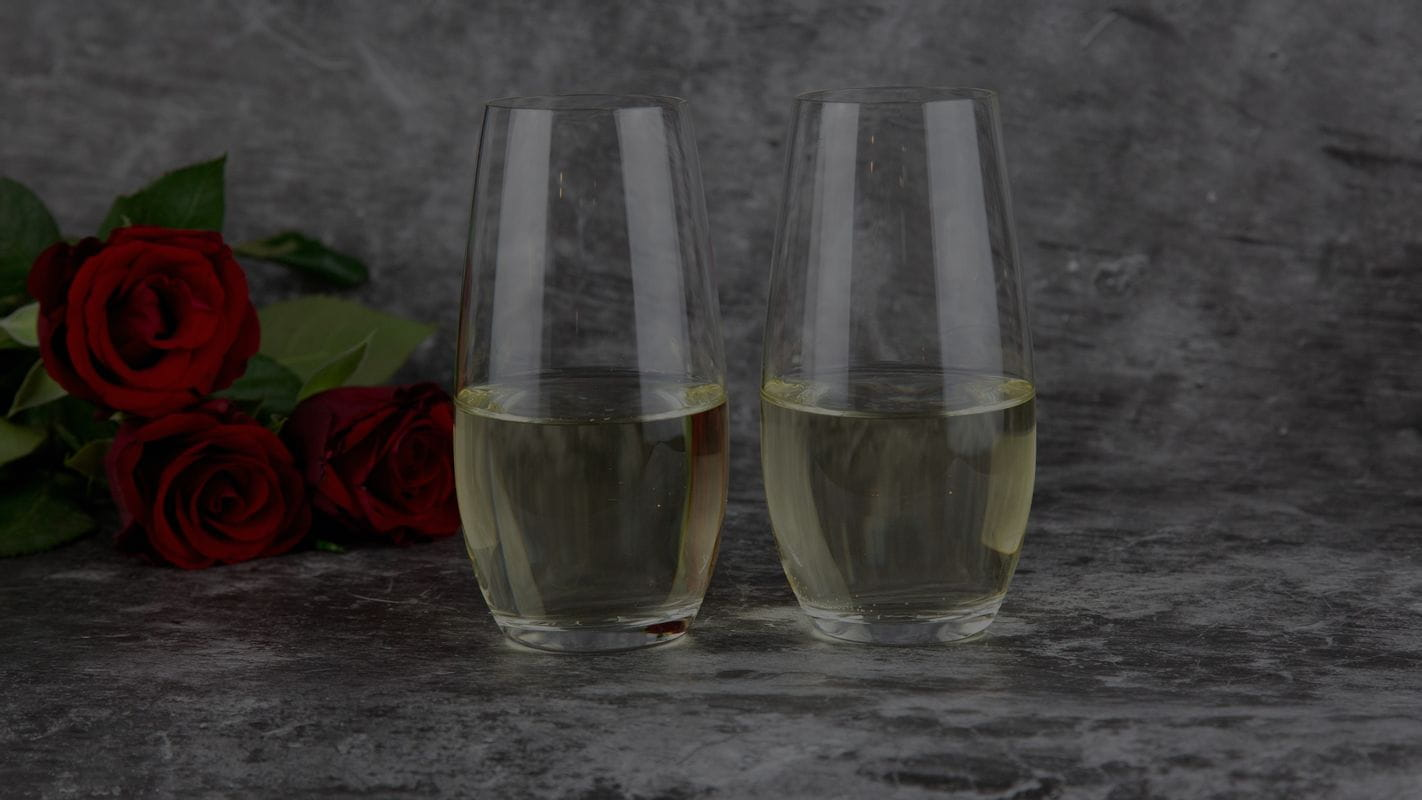 Two filled RIEDEL O Wine Tumbler Chmapgne Glasses, with a grey background and a bunch of red roses on the left side