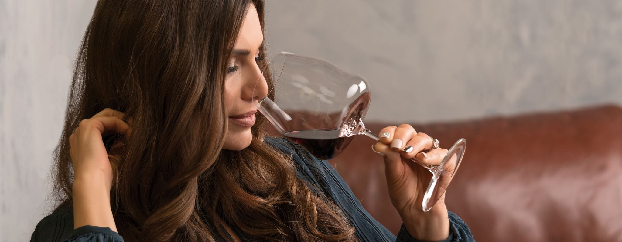 Brunette woman sits on a brown leather couch and smells with closed eyes red wine from a RIEDEL Winewings Pinot Noir glass.